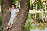 Portrait of a smiling girl sitting on tree at park