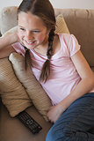 Smiling girl sitting on sofa in the living room