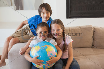 Portrait of happy kids with globe in living room