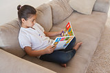 Relaxed girl reading storybook on sofa in the living room