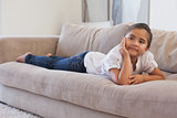 Relaxed young girl lying on sofa