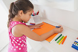 Young girl drawing on orange paper