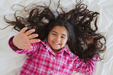 High angle portrait of smiling girl lying in bed