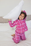 Happy young girl holding up a pillow in bed