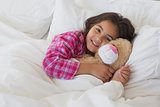 Portrait of a smiling girl with stuffed toy resting in bed