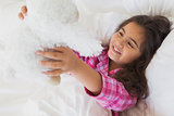 Smiling girl with stuffed toy resting in bed