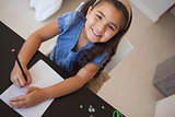 Portrait of a young smiling girl drawing on table