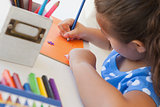 Close-up of a girl drawing on orange paper