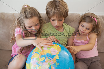Three kids with globe sitting in living room