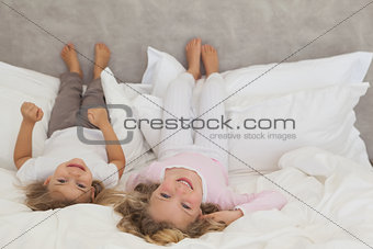 Portrait of two smiling kids lying in bed
