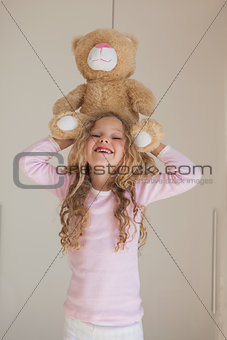 Portrait of happy girl holding stuffed toy over head