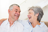 Retired couple sitting on couch smiling at each other