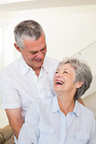 Retired couple embracing and smiling at each other
