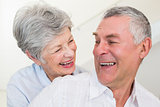 Retired couple smiling at each other and hugging