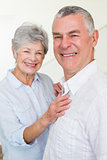 Cheerful retired couple looking at camera