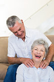 Man giving his senior wife a shoulder rub who is smiling at camera