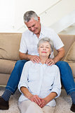 Man giving his relaxed senior wife a shoulder rub