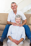 Man giving his relaxed senior wife a shoulder rub smiling at camera