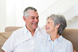 Senior couple sitting on sofa smiling at each other