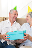 Senior couple sitting on couch wearing party hats holding a gift