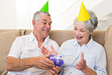 Senior couple sitting on couch celebrating a birthday