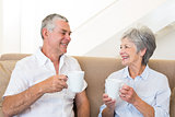 Senior couple sitting on couch drinking coffee