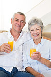 Senior couple sitting on couch drinking orange juice