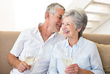 Senior couple sitting on couch drinking white wine