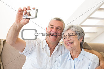 Senior couple sitting on couch taking a selfie