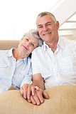 Retired couple holding hands on couch smiling at camera