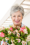 Retired woman holding bouquet of flowers smiling at camera