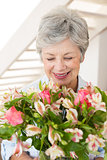 Retired woman holding bouquet of flowers and smiling