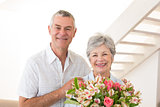 Senior couple smiling at camera holding bouquet of flowers