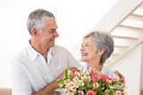 Senior couple smiling at each other holding bouquet of flowers