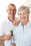 Senior man offering a rose to his partner smiling at camera