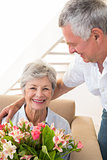 Senior man giving his partner a bouquet of flowers smiling at camera