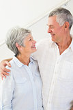 Happy retired couple standing and smiling at each other