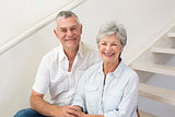 Senior couple sitting on stairs smiling at camera