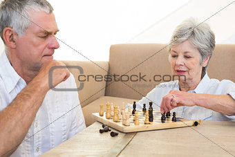 Senior couple sitting on floor playing chess