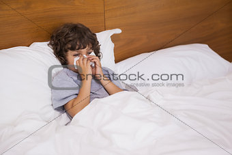 Little boy suffering from cold as he lies in bed