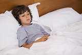Sick child with thermometer resting in bed