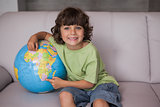 Portrait of a happy kid with globe in living room