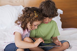 Boy and girl using digital tablet in bed