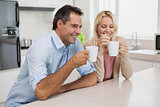 Smiling couple drinking coffee in kitchen