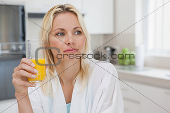 Thoughtful woman with orange juice in kitchen