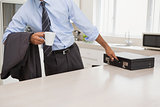 Well dressed man with coffee cup picking briefcase in kitchen
