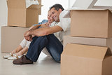 Smiling couple sitting amid boxes in new house