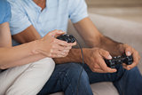 Close-up mid section of couple playing video games