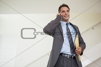 Smiling businessman using cellphone