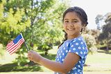 Girl holding the American flag at park